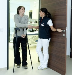 CNA greeting patient on crutches
