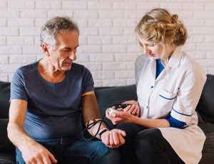 CNA taking blood pressure of senior patient
