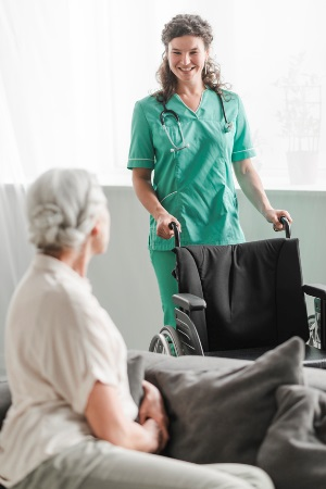 CNA holding wheelchair for senior female patient